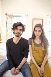 Portrait of couple sitting on bed at home - CAVF02067