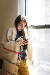 Woman using smart phone while standing by window at home - CAVF02070