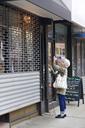 Senior woman opening shop shutter - CAVF02139