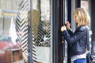 Side view of woman locking padlock on store door - CAVF02142