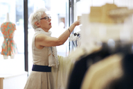 Senior woman shopping in boutique store - CAVF02157