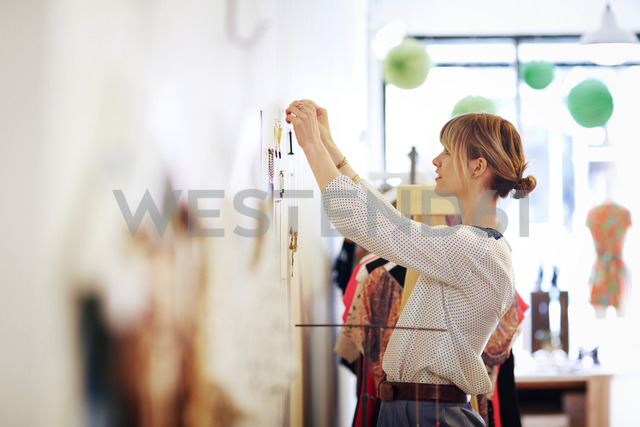 Woman arranging necklace on wall in store - CAVF02166