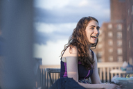 Cheerful woman laughing while sitting on chair against sky - CAVF02247