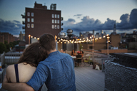 Rear view of couple relaxing on building terrace during sunset - CAVF02253