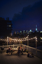 High angle view of friends enjoying on building terrace at night - CAVF02256