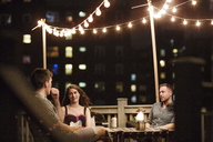 Friends talking while sitting on building terrace at night - CAVF02265