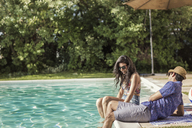 Happy couple talking while sitting at poolside - CAVF02274