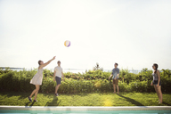 Cheerful friends playing with ball in backyard against sky - CAVF02277