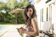Portrait of happy woman using mobile phone while standing in backyard - CAVF02280