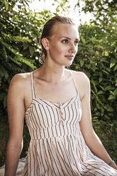 Thoughtful woman looking away while sitting in backyard - CAVF02286