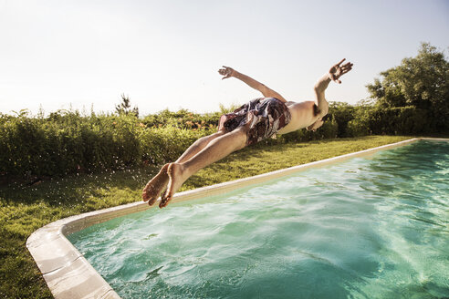 Man jumping into swimming pool against clear sky - CAVF02289