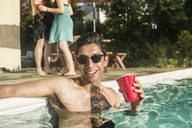 Happy shirtless man in sunglasses holding drink while standing in pool - CAVF02295