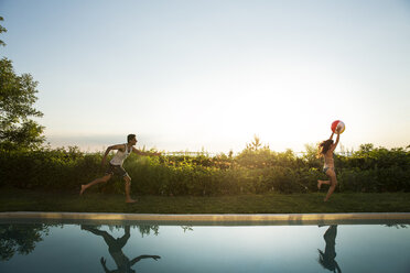 Woman with ball running at poolside while man running behind - CAVF02313
