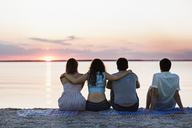 Rear view of friends relaxing at beach during sunset - CAVF02319