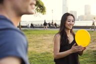 Couple playing with plastic disc in park during sunset - CAVF02328