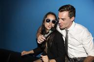 Happy couple singing karaoke in nightclub - CAVF02331