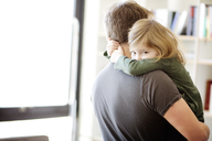 Portrait of daughter embracing father at home - CAVF02400