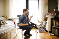 Side view of father playing with daughter at home - CAVF02412