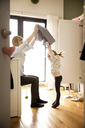 Mother changing daughter's dress at home - CAVF02418