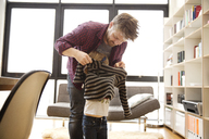 Father assisting daughter in wearing sweater at home - CAVF02445