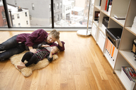 High angle view of father and daughter lying on floor at home - CAVF02448