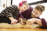 Father and daughter looking at mobile phone while lying on floor in home - CAVF02451