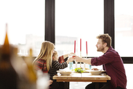 Family raising toast at dinning table in home - CAVF02457