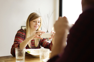 Woman using mobile phone while sitting by man at dining table in home - CAVF02460