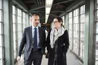 Businessman and businesswoman walking at railroad station - CAVF02463
