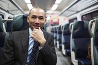 Happy businessman looking away while traveling in subway train - CAVF02466