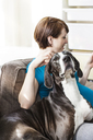 Pregnant woman with dog sitting on sofa at home - CAVF02595