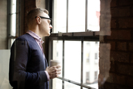 Businessman holding disposable cup while standing by window in office - CAVF02616