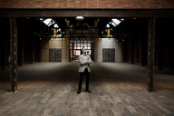 Businessman with arms crossed standing in empty warehouse - CAVF02634