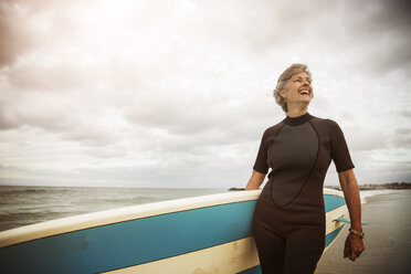Happy woman carrying paddleboard while standing at beach against sky - CAVF02676