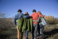 Rear view of happy friends walking on field - CAVF02736