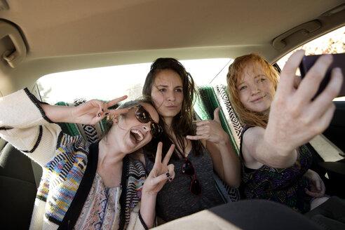 Happy friends taking selfie while sitting in car - CAVF02751