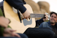 Midsection of man playing guitar while sitting with friend - CAVF02760