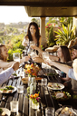 Happy friends toasting wineglasses at dining table on porch - CAVF02784