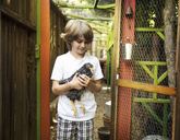 Boy holding hen in backyard - CAVF02811