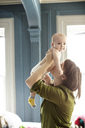Woman lifting daughter while standing in bedroom - CAVF02844
