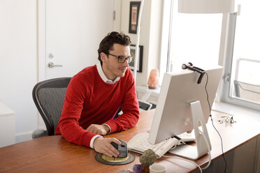 Businessman using computer on table in office - CAVF02847