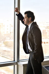 Side view of thoughtful businessman looking through window - CAVF02850