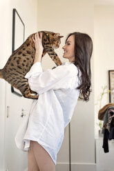 Smiling woman playing with cat at home - CAVF02859