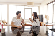 Cheerful couple drinking coffee on table at home - CAVF02862
