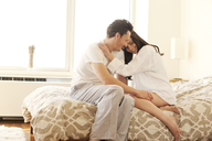 Happy couple relaxing on bed at home - CAVF02868