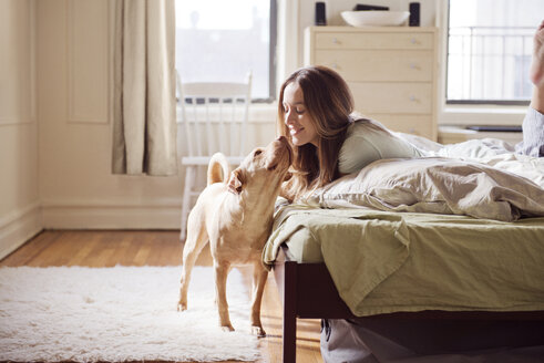 Young woman playing with dog in bedroom - CAVF02886