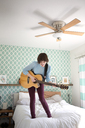 Happy woman playing guitar while standing on bed at home - CAVF02970