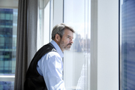 Thoughtful businessman looking through window while standing at hotel room - CAVF03003