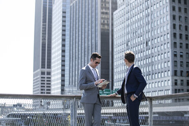 Businessman using tablet computer while standing friend against city buildings - CAVF03054