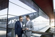 Businessmen using tablet computer while standing outside building - CAVF03075